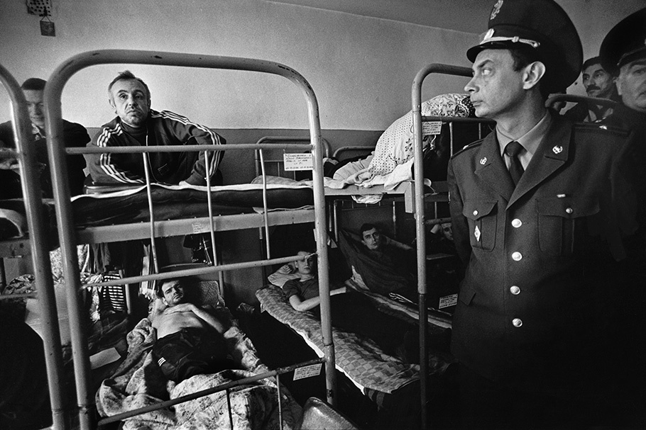 A guard with prisoners on bunk beds.