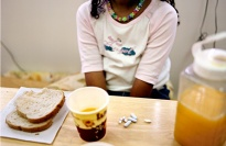 A child at a table with pills and food.